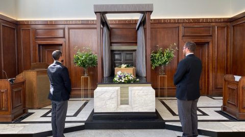 Coffin before cremation with two onlookers - Chelsea Funeral Directors